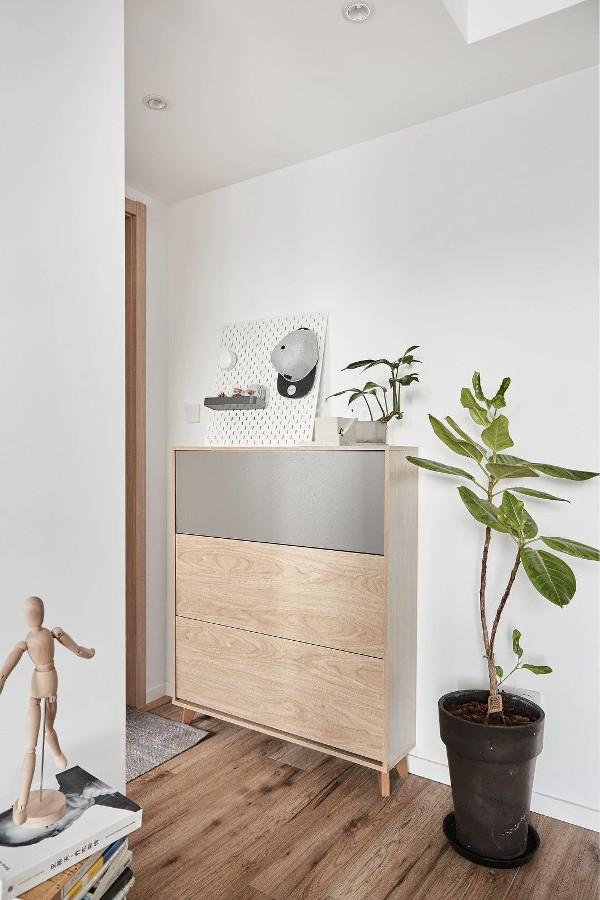 玄关距离短且狭窄,并不适宜放置大鞋柜。北欧风格的鞋柜和地毯体积小颜色轻,缓解了小空间的压抑感。