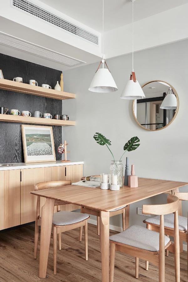 从镜中可以看到厨房的黑框玻璃谷仓门。玻璃材质保证了餐厅的采光,搭配黄铜镜食用更佳