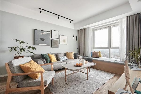 夹边套的客厅朝向偏北,采光不是特别好,因此客厅的设计重点是明亮。轨道灯代替主灯,搭配大飘窗和色调轻浅的家具,轻盈不失温馨。