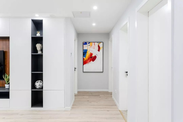 玄关对着的走廊位置,在走廊尽头挂一幅鲜艳的装饰画,城电视墙的收纳柜加入一个黑色的格架,整个空间显得简单实用好优雅。