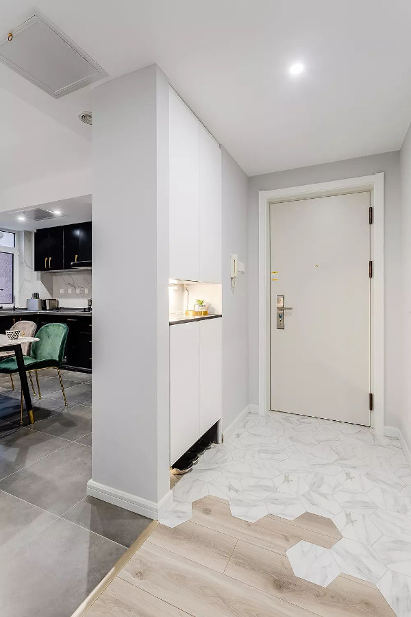 玄关旁边是开放式的餐厨空间,以鞋柜作为空间隔断,既让玄关空间独立出来,又实现了鞋柜收纳功能。暖灰色的墙面空间感,给人以简约温馨的舒适,结合六边砖、灰色砖与木地板拼接的地面,呈现出一个轻松自然的空间感。