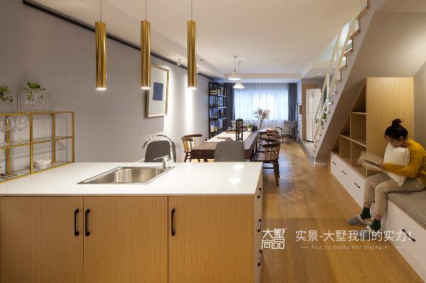 进门门厅一侧因地制宜,在楼梯下方以组合柜的形式呈现,可满足书籍物品收纳、休憩空间、西厨操作台、衣物储纳等多种功能。