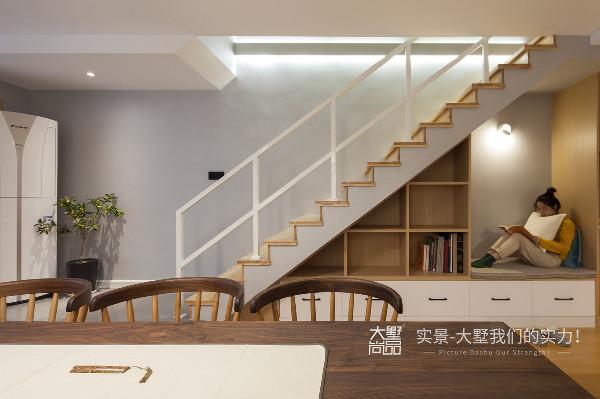 楼梯下方的组合式收纳柜预留了休息区域,平时可以窝在这里看看书,暖色光源充分考虑到了眼睛的舒适度。 楼梯墙面的灯带在解决了夜里的照明的同时,也给空间带来几分层次感。