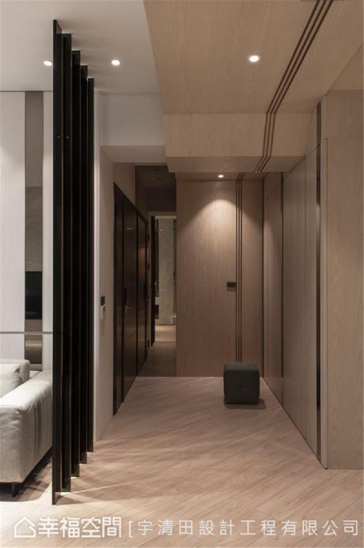 视感延伸 玄关收纳与墙体整合,打造简约俐落立面。运用木皮、金属饰条由壁面延展至天花,再落于对向通往私领域过道的端景墙,微妙引导入内的视觉及动线。