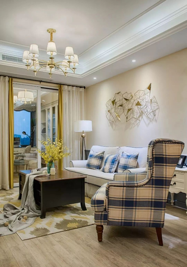 客厅地面通铺木色地板,书房清玻门片将采光自然投射进休闲客厅,奶咖色乳胶漆墙面在明亮的灯光下,更显空间温馨柔和