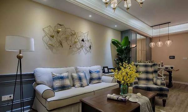浅色布艺沙发搭配蓝色格子靠枕,金色铁件墙饰,充满设计感,与空间中的金属灯饰相互呼应,提升空间格调