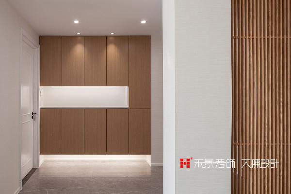设计师对室内动线进行重新梳理,在入户门厅以通透的木格栅做隔断,既有古朴雅致的风韵,又能产生通透与隐隔的互补作用。留出的空间做了嵌入式玄关柜,中间留空放小物件,上下储物。