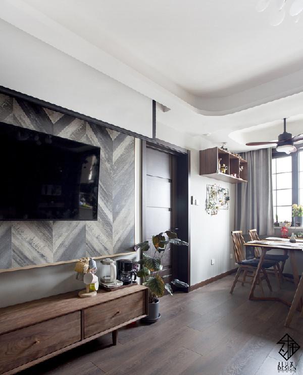 电视墙和餐厅在客厅的西墙,两个功能区之间是儿童房的房门。圆角吊顶包住了顶部的空调管道,这种处理办法并不会有压低空间的感觉,反而会使整个空间拉开层次,增加顶部的进深。