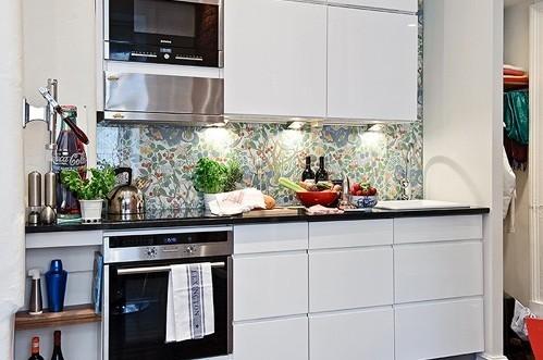 这是种最为惊艳的墙纸装饰,白色的厨柜清净清爽,而内部偏绿色的繁花墙纸却大放异彩!装饰性非常的棒!