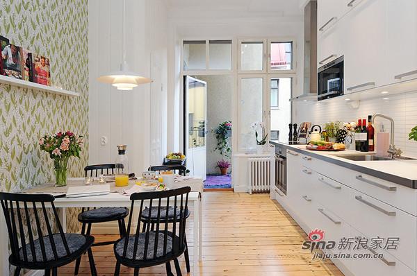 镶板门和异型厨房碗柜形成鲜明对比的白色时尚的厨房
