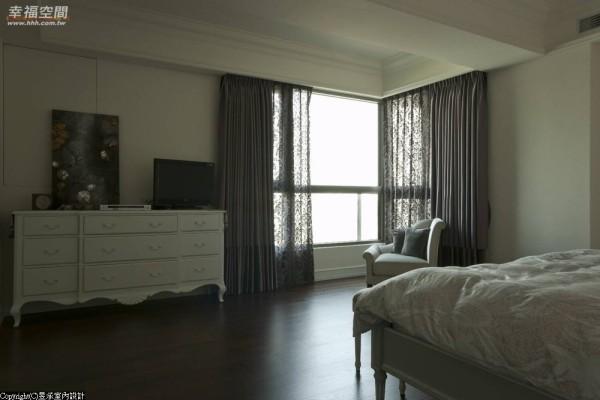 映入眼帘的是线条柔美的造形腰柜,兼作化妆台及电视柜,上方原有的窗户也技巧地掩入墙面设计中