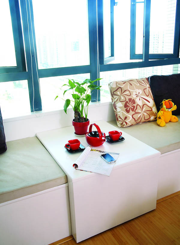 原凸窗改成休闲台,两边是订制的活动式布艺软垫,中间做L型活动木制茶台。靠背及侧墙均贴上白漆面板(这样更便于打理),使得客厅宽敞、舒适。