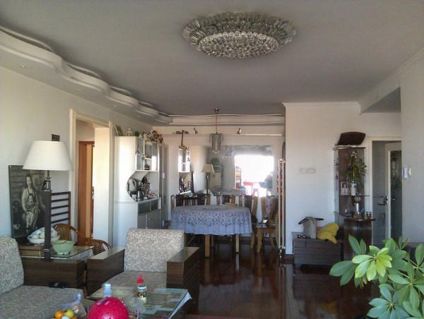 蝴蝶型凹槽吊顶,曲线的造型给中规中矩的中式风格添加了几分柔和,餐桌上方的照片墙以旁边的中式画遥遥相对,营造了一个多彩的就餐环境.