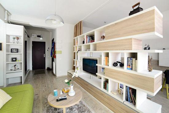 电视背景墙:敞开式收纳柜与挖空格子相结合的电视背景墙发挥着强大的收纳功能,同时也成为了客厅与卧室的隔断墙,其不规则的外观更为空间增添了立体感和灵动性。