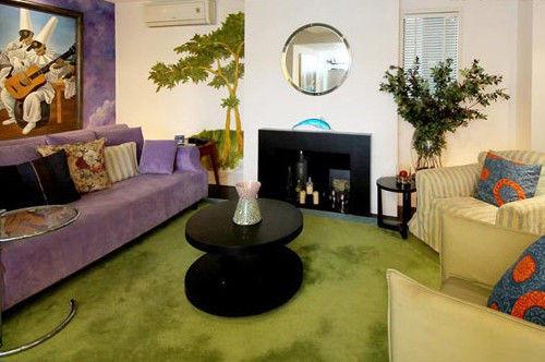 """装饰亮点:绿色地毯(地毯装修效果图)和同色系布艺沙发构成了一个春天般清新感的空间。主人巧妙地搭配色彩浓厚的紫色沙发和背景墙,撞色的效果更能突出居室""""万物复苏、大地回春""""的意境。"""