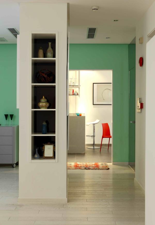 门厅设计原有格局拆除,中间只保留了方形的通风口和承重墙体,形成了小空间的迂回。镜面不锈钢装饰的墙面背后是小型的客卫,把卫生间的门消隐在环境中,粉绿色的墙面与写意空间灰色的矮柜相互协调。