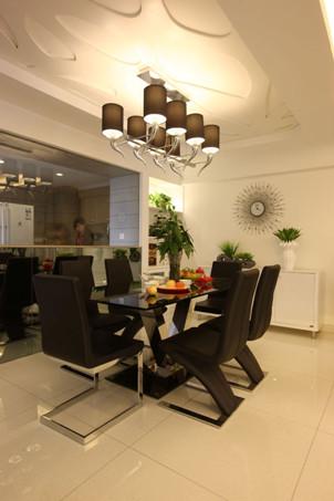 客厅与餐厅相邻,功能区区分不明显。设计师通过顶部吊顶设计,横纵两向增强空间层次感,实现了区域划分。