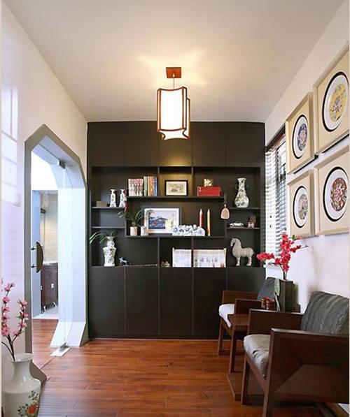 在把开放式的书房中,靠墙摆放了两把舒适的椅子,墙面上挂满了装饰品。黑棕色的大书架占满了整面墙。有着曲线美的灯饰照耀着木地板。