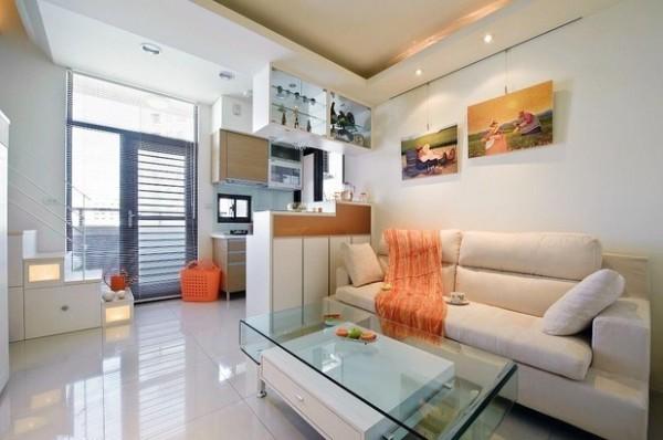 柜体是白色烤漆的,布艺沙发购买米白色的款式,用整体的白色调扩大空间感。茶几与吧台吊柜对应,玻璃台面可透视可反照,既美观又实用。