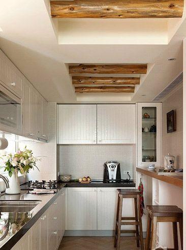 米白色系的厨房,橱柜四周收拾的整洁干净,只有右手边的橱架上摆放了各种瓶瓶罐罐和小杂物。