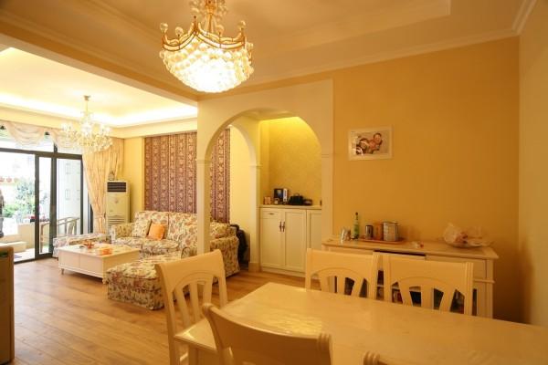 整个房间使用暖黄色为基调,营造空间的温馨感。墙面没有使用过多的造型。沙发背景墙用相对深色的墙纸作点缀,餐厅墙上以一张全家福温馨的照片呈现。简单的水晶灯,丝毫不显张扬与贵气,另有一番雅致的韵味。