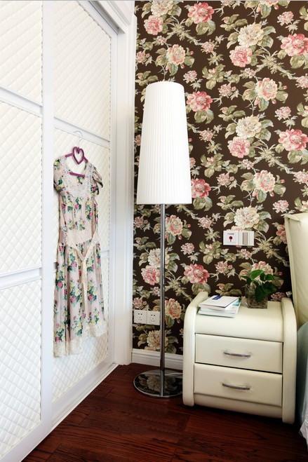 床头的背景采用的是印花壁纸,沉稳的主色调配上粉色的印花,彰显出业主的女心澎湃,大衣柜上业主的碎花裙子正好与床头背景温和统一,使得整个空间完美的柔和在一起。