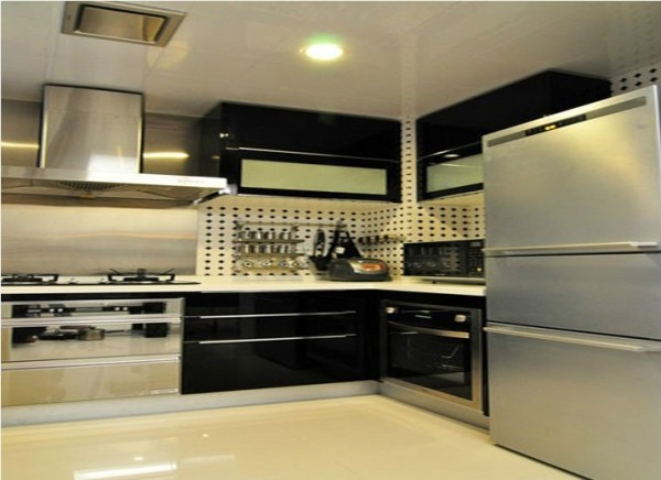 厨房的空间讲究对称且划分简单合理,给了主人们更充裕的自由活动空间。黑白拼搭的瓷砖和钢琴漆的橱柜使平日枯燥的厨房有了酒吧的感觉,让不爱下厨房的80后从此爱上厨房。