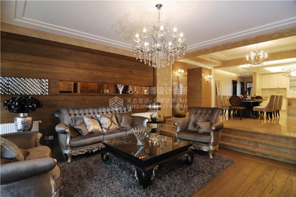 客厅的顶部以华丽的水晶吊灯、大气豪华的缎面沙发、黑色的欧式茶几给整个空间以高贵华美的定位.设计师喜欢大自然的元素,讨厌刻板与矫情的设计,大胆的将木地板用到客厅的墙面装饰上,与墙纸相比,更显得高贵大方.