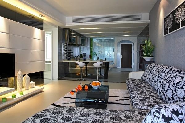 客厅采用深色沙发和浅色的地毯形成对比。电视墙背景造型并设置有射灯美观大气 ,台前放装饰品 ,增加了一份情调 。