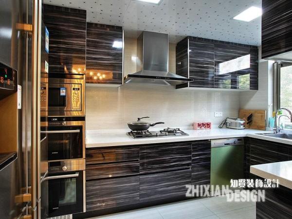 厨房以黑棕色为主色调,大气沉稳,有效的克服了厨房的烟火之气。作为典型的现代厨房做派,厨房各式装备齐全,一体化设计的橱柜构建出厨房的整个格局,烤箱等一系列改善型器具有序排布,让厨房功能更趋完美