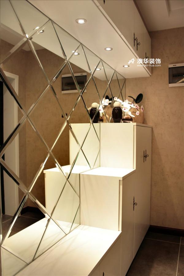 阶梯型储物柜少了呆板沉闷,富有设计感,此外还可作为展示架。配上顶部的横排储物柜,超大的容量,满足了主人的储物需求。     加入菱形镜面的置入,视觉上拓宽了走道的宽度,更添时尚感。
