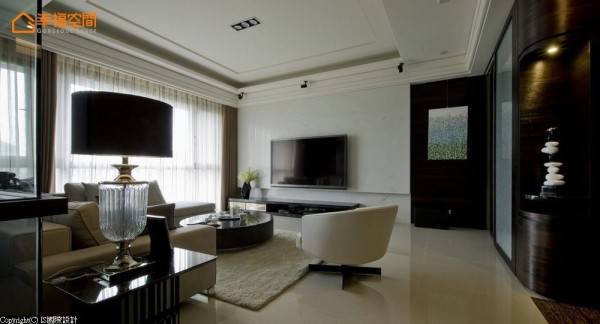 呈现石材清爽利落的纹理的白色电视主墙,与一旁佛龛前的廊道区块,以深色木皮衔接,搭上挂画营造端景效果。