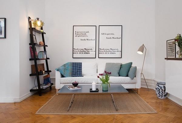 沙发区隐藏在凹形墙内,拥有一片静谧天地。靠墙还有一个梯形摆放柜,加一盏明亮的小灯,客厅便有了充足的光线