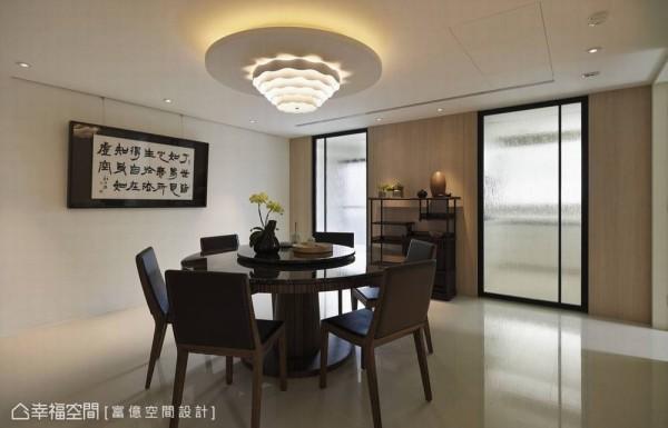 加大尺度的圆桌是亲友共聚、分享读书心得的第二空间,通往厨房与后储藏阳台的乱纹玻璃门片对称规划,并引进敞亮日光明亮无对外窗的餐厅。