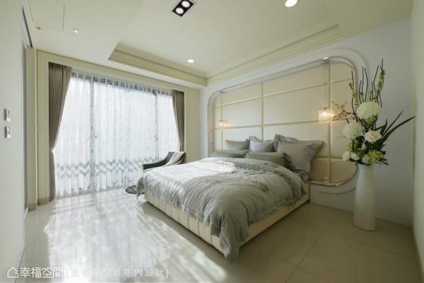 轻浅调性的主卧房,洒下窗外温暖的日照,床头的部分采用以ㄇ字框架来形塑,并使用裱布与吊灯强调细腻的工法。