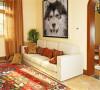 北京别墅装修——家庭起居室。相对私密的家庭空间,颜色比一层的客厅略显柔和,但依然延续了色彩浓烈的特征。沙发后墙上悬挂的画其实是一副巨大的拼图画,由无数主人的小照片组成,富有艺术感和趣味性。