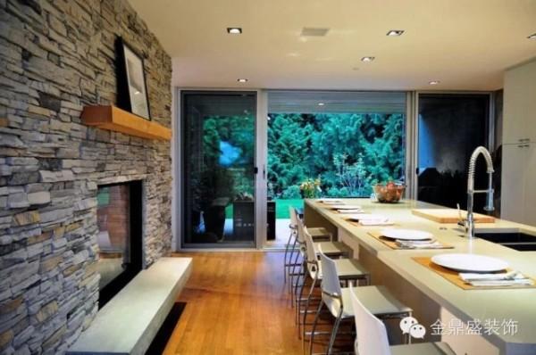 【宁静的现代森林私家住宅-餐厅】石墙的另一侧设置为早餐厅,大面积的落地窗引入更多阳光让早餐时光更加美好,享用一顿高效而营养的早餐在这里变得格外惬意。