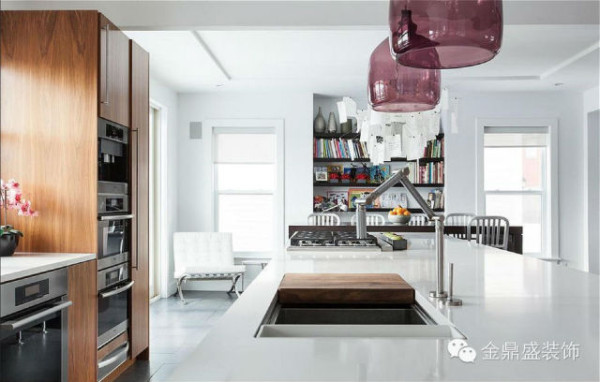 实木贴面的橱柜、灶台、洗菜台面等占据了所有的厨房空间,圆肚杯型的琉璃顶灯悬挂在大理石洗菜台面之上,通透、轻盈。