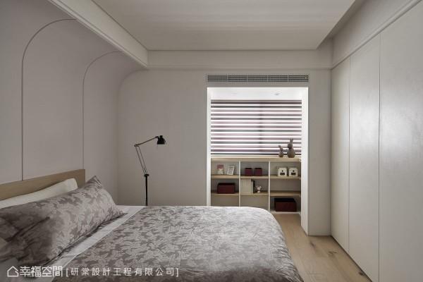 空间两侧都有梁体,床头上方以一道弧线修饰,跳色的主墙成为空间主要氛围,衣物收纳构成床尾立面,窗前则有独立的置物展示区。