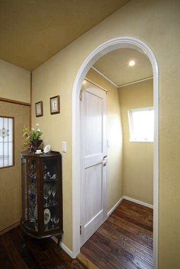 拱形的入口,地中海风格浓厚。木质边框的玻璃收纳柜,独特美观,引人眼球。鹅黄色的一面墙壁,给人舒适温馨之感。嵌入式壁灯,现代感十足。
