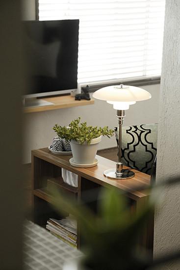 透过窗户看向客厅,又有另一番韵味。开放式的分层收纳柜,使得物品的摆放更显整齐。一套蓝白相间的陶瓷杯具,体现出主人的审美品位。