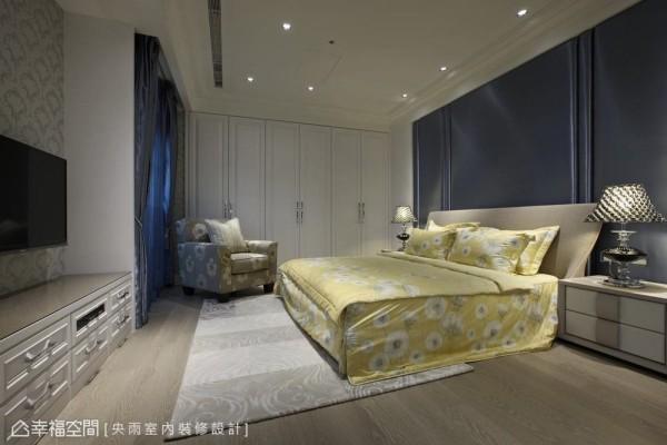 不同与主卧室的连续口字框造型,这间卧房以蓝色的绷布处理相同的对称语汇,增添时尚精品质感。