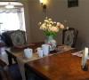 餐厅装修设计中全套实木餐桌椅体现了业主对生活品质的讲究,桌旗、餐桌垫、瓶花体量虽小,但经过精心布置,亦能妆点出浓郁生活气息。