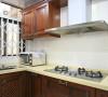 墙壁上挂着置物柜,方便储藏厨具,用餐材料,厨柜皆用红木,十分有质感,而台面则采用鹅黄色大理石,是为了凸显厨房的窗明几净,同时保持干燥防止木质受潮