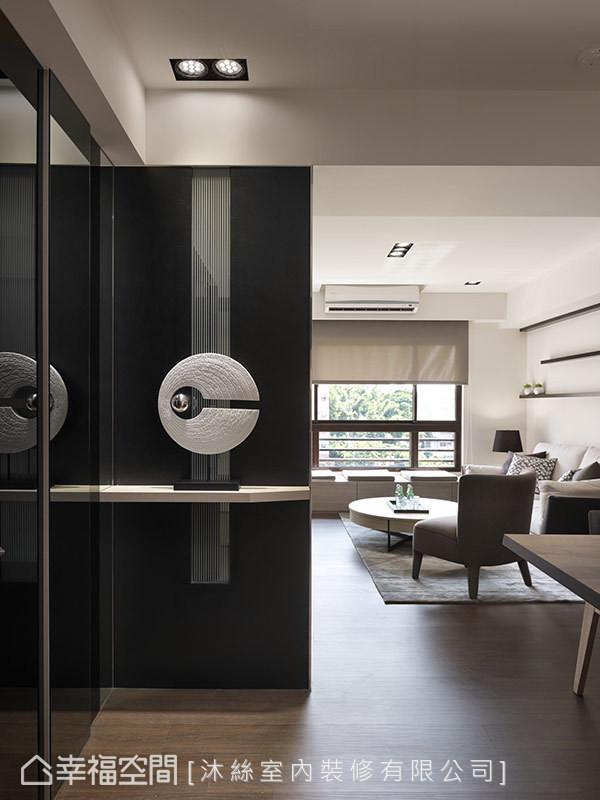 以灰镜取代传统的鞋柜门片,并利用实木及镜面不锈钢等媒材,创造大器利落的迎宾印象。