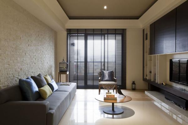 客厅的装修:原生态的白墙,搭配灰色的布艺沙发,空间随意舒适。