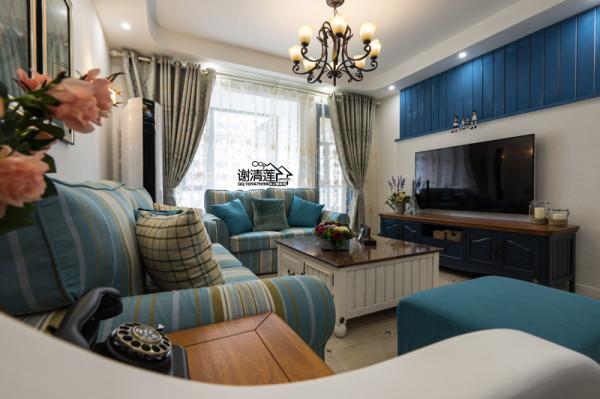 在客厅区域中设计师用蓝色布艺沙发,木制茶几、边几,地中海风格的吊灯整体搭配,体现地中海风格的色彩结合了海与天明亮,在简单中也能体会到丰富。