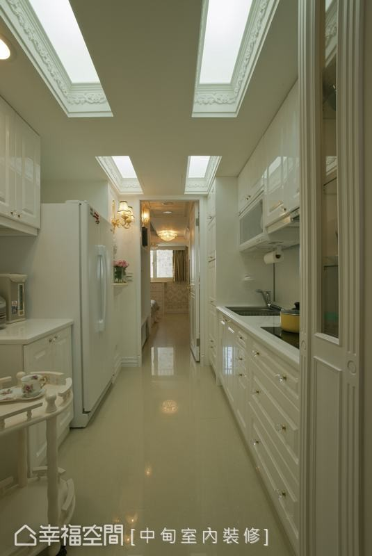 白色的开放厨房,也作为连结客厅、书房和主卧室之间的走廊。