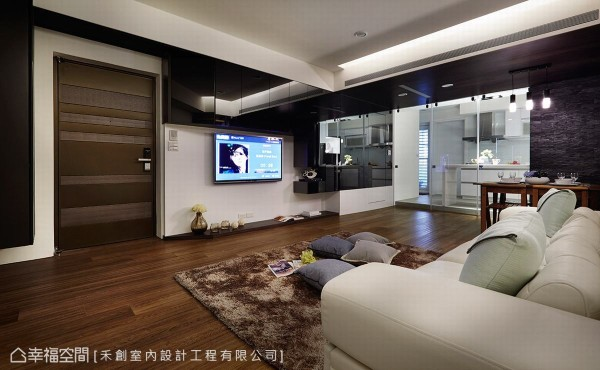 于电视墙上方规划黑色烤漆玻璃柜体,于光影反射中达到空间放大的视觉效果,而悬吊式的设计手法也巧妙化解屋高不足的压迫感。