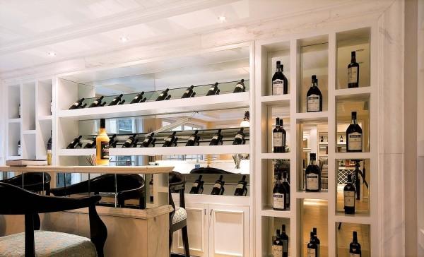 墙面整体的酒柜设计,白色的框架和黑色的酒瓶相互搭配,整体的感觉美观、和谐。
